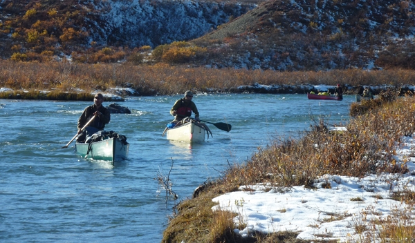 Caoneing out in canoes loaded with moose meat.
